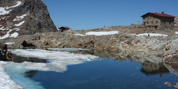 Nach einem schneereichen Winter sind die Schmelzwassertümpel unter der Hütte noch mit Schneeresten bedeckt.