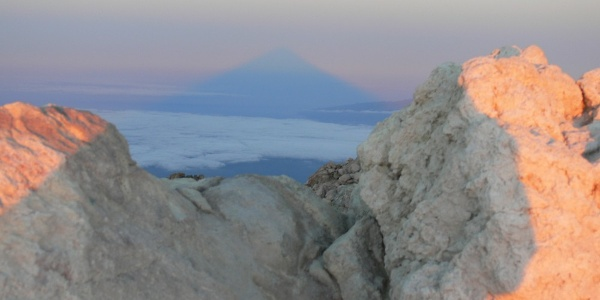Bei Sonnenaufgang wirft der Teide einen Schatten auf den Atlantik