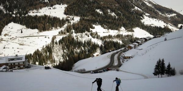 Ein große Wiese führt vom Parkplatz (unten) zum Waldrand. Im Hintergund der Sumpfkopf (2341 m).