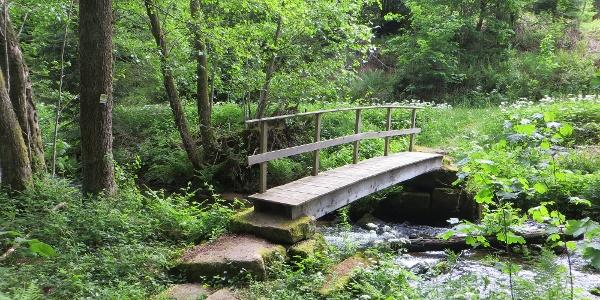 Über eine urige Holzbrücke quert man die Kleine Enz