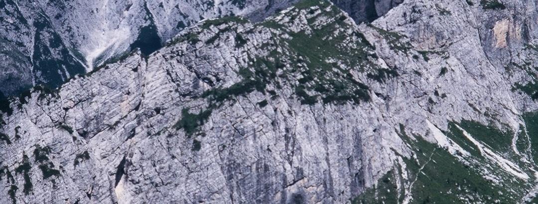 Un puntino rosso tra i verdi sotto la parete del Col Lanar: è il bivacco Damiana. Sullo sfondo il Siera Spitz e il Piccolo Siera