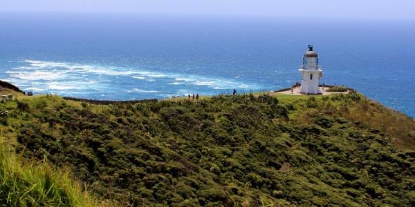 Leuchtturm auf dem Cape Reinga, im Hintergrund treffen Tasmansee und Pazifik aufeinander