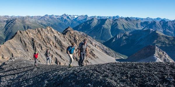 Auf dem Gipfelgrat des Piz Quattervals, Blick nach Norden. Im Mittelgrund der Spi da Tantermozza, im Hintergrund die Berge der Silvrettagruppe.
