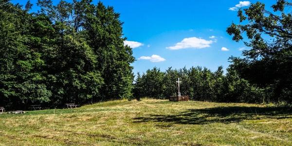 A kereszttől balra találjuk az erdei pihenőhelyet; mögötte kanyarodik el a Kéktúra