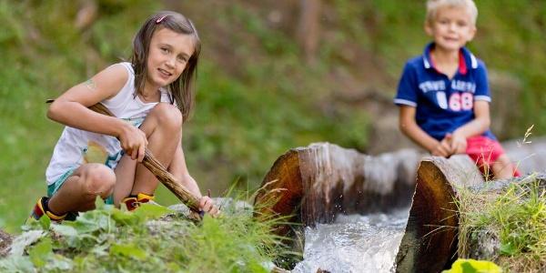 Kinder spielen am Suonenerlebnis Zauberwasser