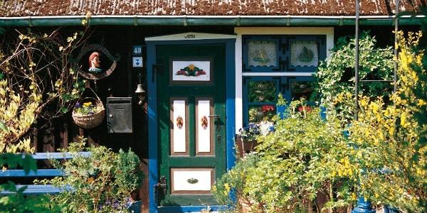 Mit Schnitzereien reich verzierte und bunt bemalte Haustür einer Fischerkate auf Fischland-Darß-Zingst