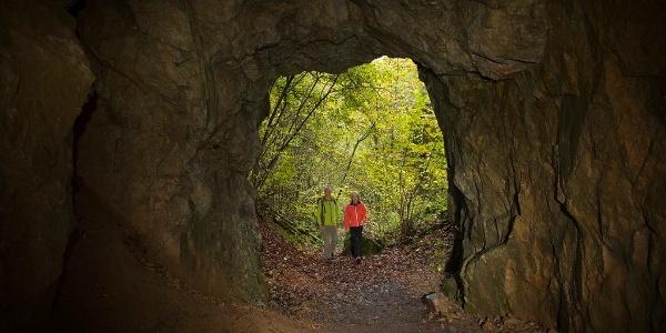 Zwei Wanderer die durch einen höhlenartigen Tunnel gehen