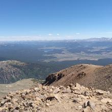 Blick vom Gipfel auf dessen Sattel mit dem Steinmandl