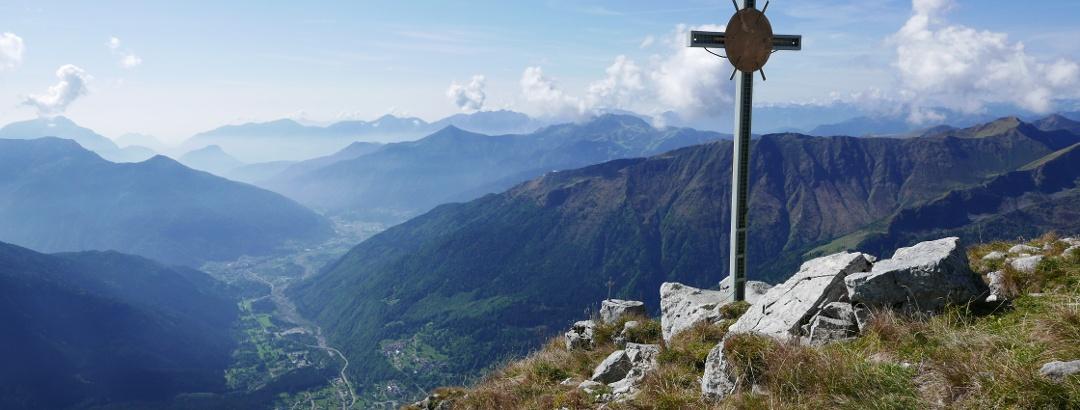 Das große Gipfelkreuz des Piz Timau mit Blick auf Paluzza