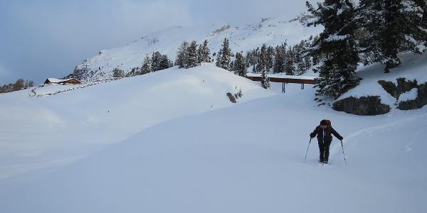 Stapfen durch den tiefen Schnee bei der Almhütte