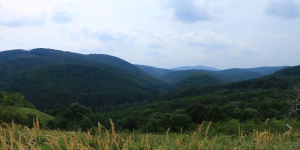 A gerincről elénk tárul az Óbányai-völgy és a fölé magasodó hegyvonulatok látványa