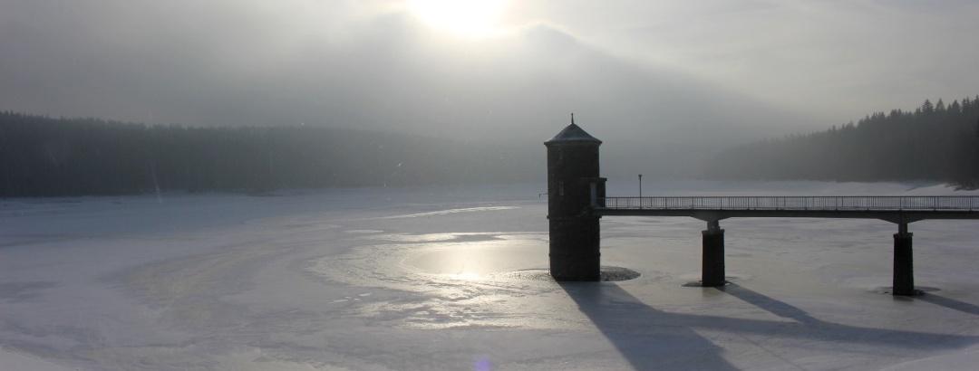 Die Talsperre im Winter mit vereistem Wasser und aufziehendem Hochnebel