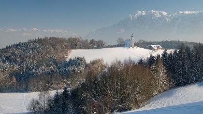<![CDATA[Kirche und Wirtshaus vor Bergkulissee: Johannishögl in Piding im Winter]]>
