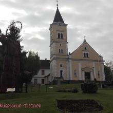 Kirche mit Franziskusstatue in Tischen