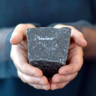 Hände, die einen Stein halten.