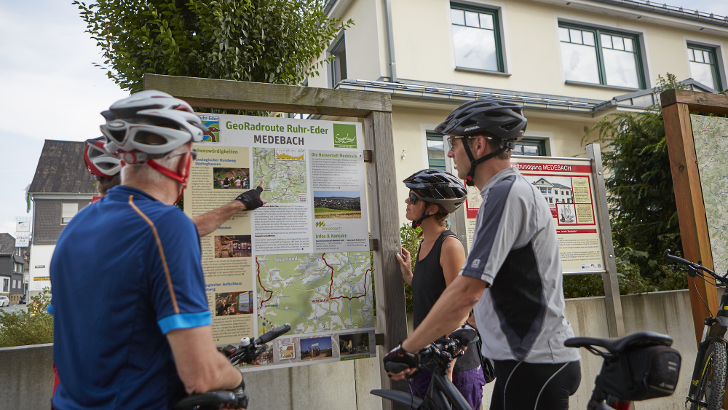 Radfahrerinnen und Radfahrer informieren sich in Medebach über den weiteren Streckenverlauf. Die öffentliche Infrastruktur in Südwestfalen mit digitaler Hilfe nachhaltig zu bewirtschaften, ist Ziel des REGIONALE-2025-Projekts.