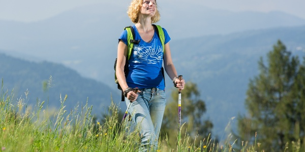 Wanderin auf einer naturbelassenen Wiese mit Landschaftszügen im Hintergrund
