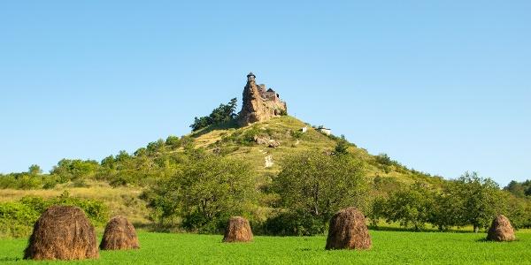 Boldog-kő sziklataréja és a rajta trónoló vár magasodik a kaszálók fölé