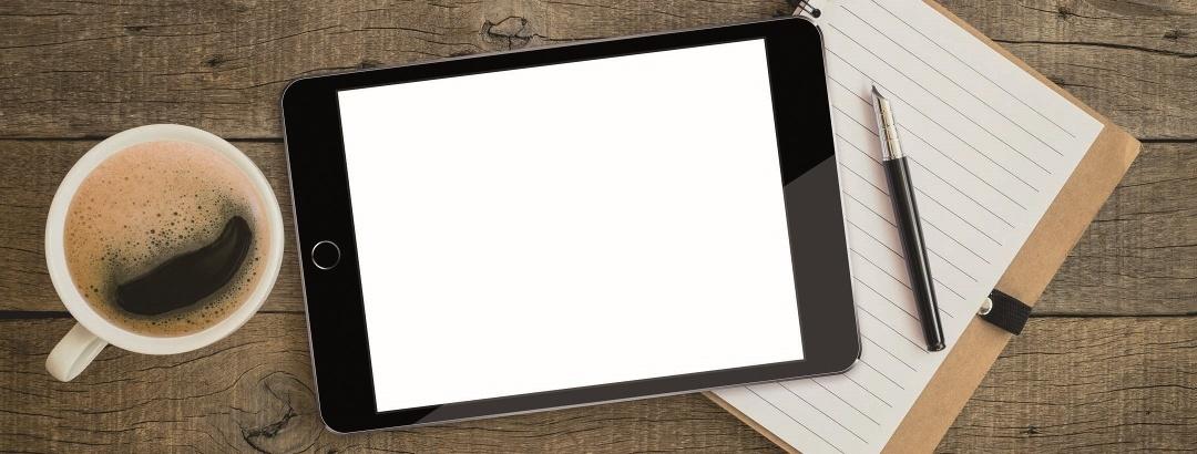 Notizblock, Stift, Tablet und Kaffeetasse