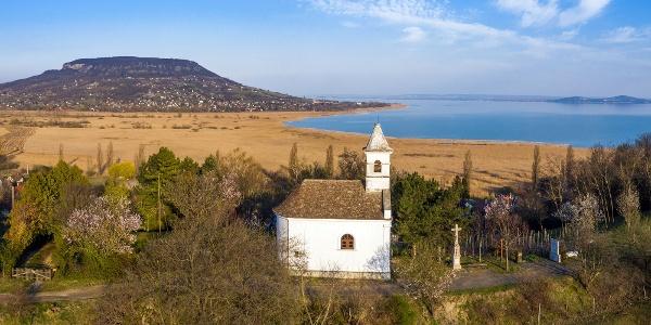 A szigligeti Szentháromság-kápolna a Rókarántón, a háttérben a Badacsony