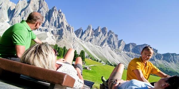 Das Freiluftkino: Holzliegen oberhalb der Geisleralm mit Blick auf die Bergkette der Geislerspitzen