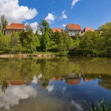 Die Wirtschaftsgebäude des Klosters spiegeln sich im Weiher