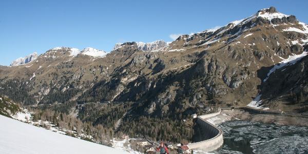 Der Beginn der Skitour führt über die Piste. Im Hintergrund der Fedaia-Stausee.